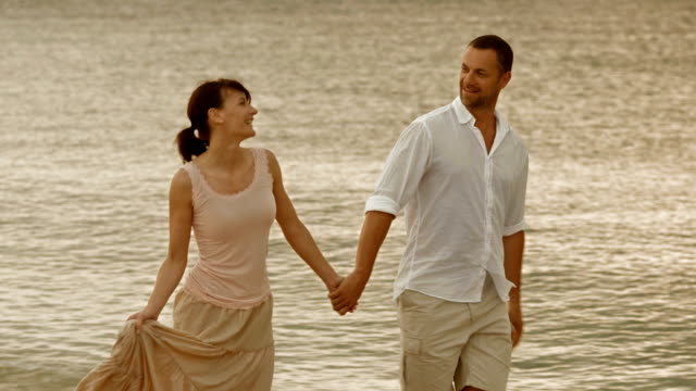 Romantic couple walking by the shore holding hands