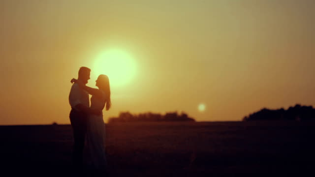 WS Romantic couple walking in meadow at sunset