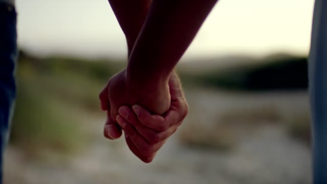 romantic couple walking on the beach. holding hands - falling in love stock videos & royalty-free footage