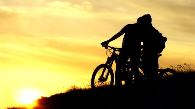 hd crane: romantic cyclists enjoying the sunset view - crane shot stock videos & royalty-free footage