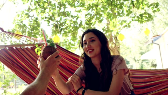 romantic date on the hammock. drinking tropical drink - hammock stock videos and b-roll footage
