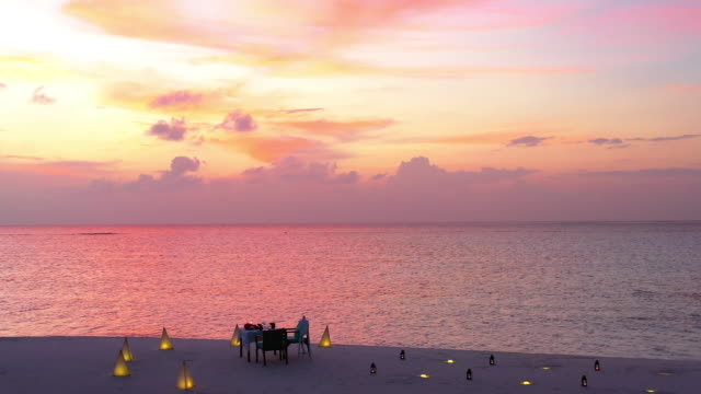vídeos de stock e filmes b-roll de romantic dinner on the beach with amazing sunset, maldives - anoitecer