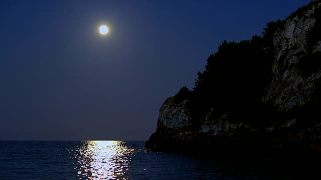 romantic fullmoon about the mediterranean sea at night on cala romantica on spanish balearic island of majorca / spain - balearic islands stock videos and b-roll footage