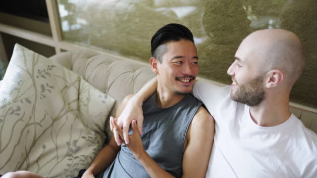 romantic gay couple embracing on sofa - remote control stock videos & royalty-free footage
