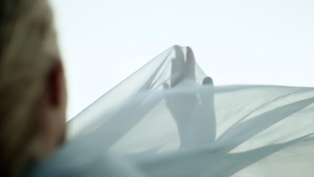 vídeos de stock e filmes b-roll de romantic girl in long dress enjoying the wind. hiding in transparent textile - textile