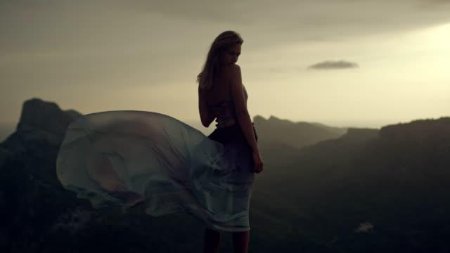 vídeos de stock e filmes b-roll de romantic girl in long dress enjoying the wind. looking at view from a cliff - model