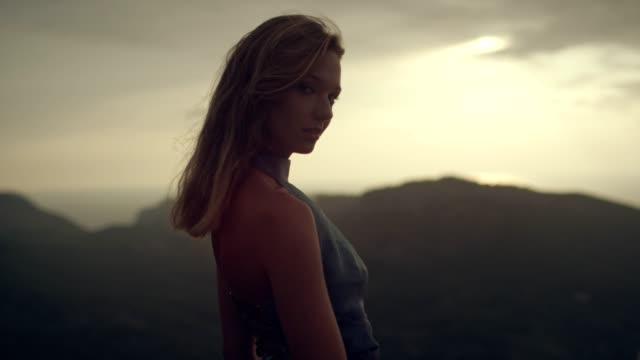 vídeos de stock, filmes e b-roll de garota romântica no vestido longo, aproveitando o vento. olhando para a vista de um penhasco - roupa formal