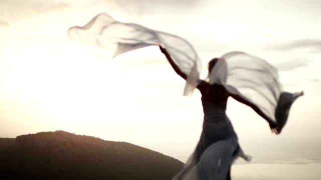 vídeos de stock, filmes e b-roll de garota romântica no vestido longo, aproveitando o vento. de pé em um penhasco - roupa formal