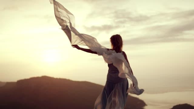 vídeos de stock e filmes b-roll de romantic girl in long dress enjoying the wind. standing on a cliff - seda