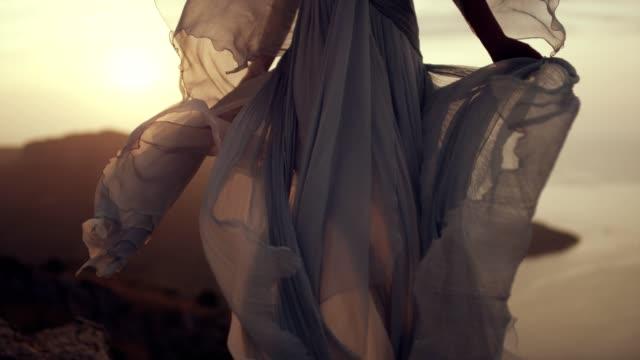 Romantische meisje in lange jurk genieten van de wind. Staande op een klif