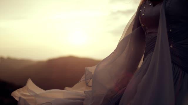 vídeos y material grabado en eventos de stock de chica romántica en vestido largo con el viento. de pie en un acantilado - vestido