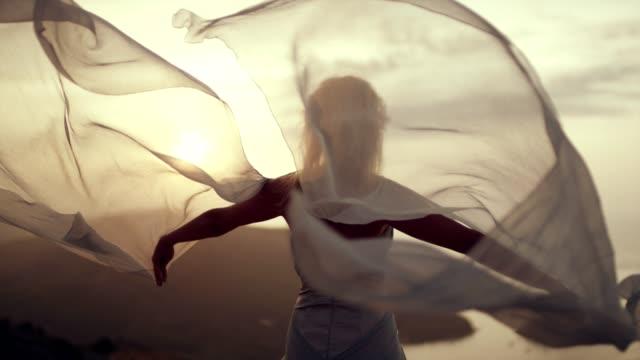stockvideo's en b-roll-footage met romantische meisje in lange jurk genieten van de wind. staande op een klif - avondjurk