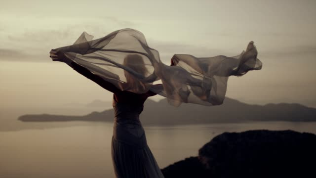 vídeos de stock e filmes b-roll de romantic girl in long dress enjoying the wind. standing on a cliff - textile