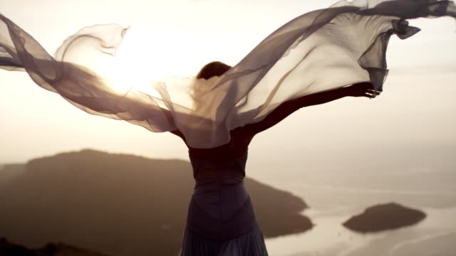 romantic girl in long dress enjoying the wind. standing on a cliff - wind stock videos & royalty-free footage