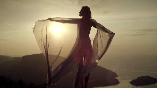 romantic girl in long dress enjoying the wind. standing on a cliff - trasparenza video stock e b–roll