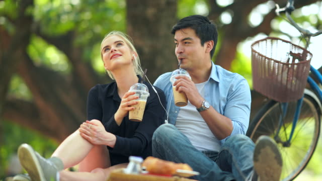romantic happy couple drink coffee   in park - coffee drink stock videos & royalty-free footage