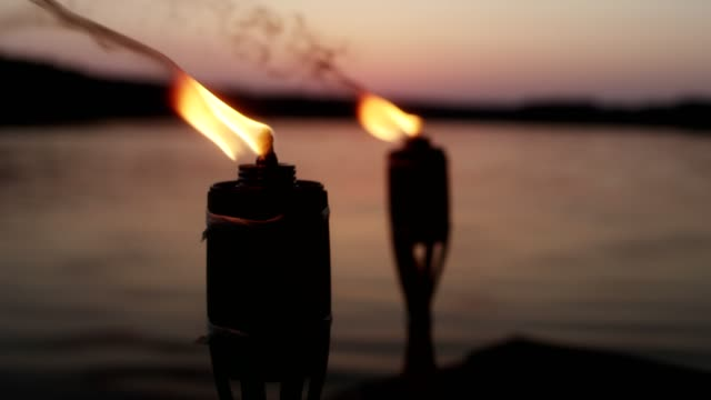 Romantic lake sunset. Burning torches on a pier