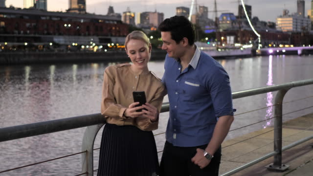 romantic latin couple enjoying city break in springtime, using phone to take selfies - puerto madero stock videos & royalty-free footage