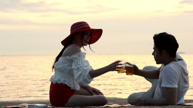 vídeos y material grabado en eventos de stock de pareja de amor romántico sentado hablando en la playa al atardecer - romance