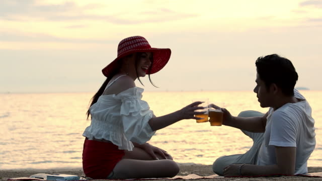 vídeos de stock e filmes b-roll de romantic love couple sit talking on the beach at sunset - romance