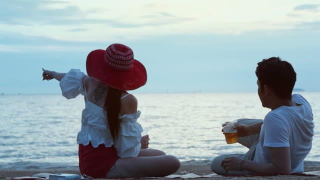 vídeos de stock, filmes e b-roll de casal de amor romântico sente-se a falar na praia ao pôr do sol - flertar