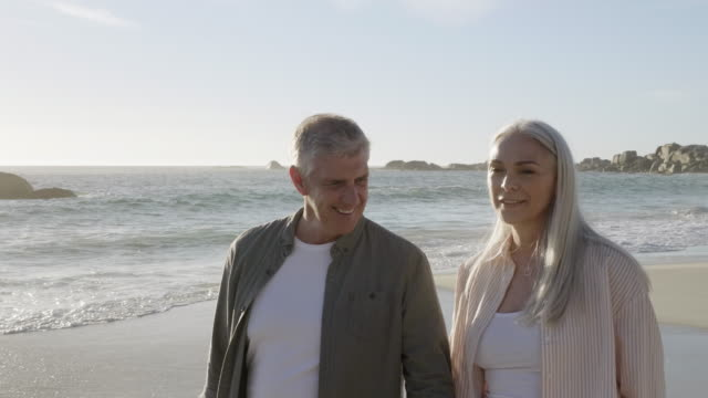 romantic mature couple walking at beach in summer - 50 59 years stock videos & royalty-free footage