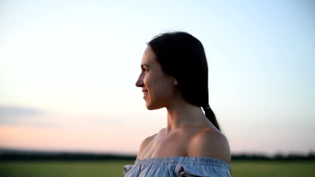 romantic  portrait of beautiful dark-haired woman in the field during sunset - back lit stock videos & royalty-free footage