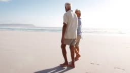 Romantic Senior Couple On Summer Vacation Walking Along Beach