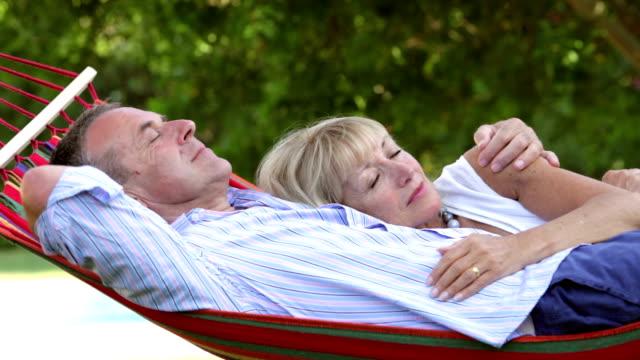 Romantic Senior Couple Relaxing In Garden Hammock Together