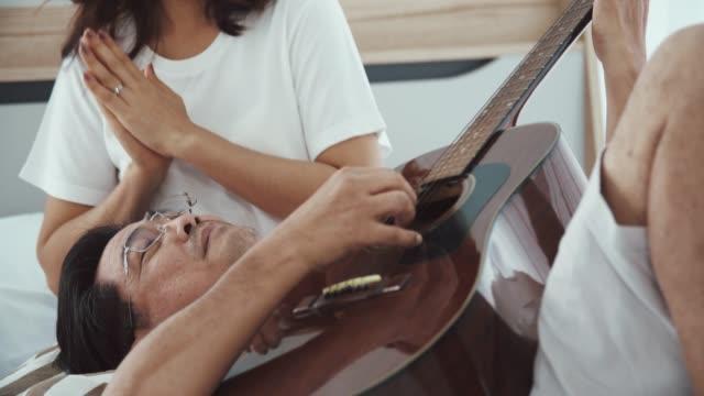 vidéos et rushes de homme aîné romantique jouant la guitare pour la belle femme aînée - guitare