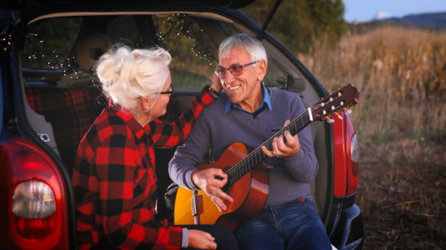 Romantic senior man playing guitar for beautiful senior woman