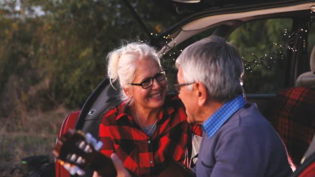 vidéos et rushes de homme senior romantique, jouer de la guitare pour belle femme senior - guitare