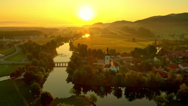 vídeos y material grabado en eventos de stock de aerial romántico pequeño pueblo en el río al atardecer - multicóptero