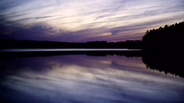 Romantic sunset above lake. Peaceful scenery with purple clouds