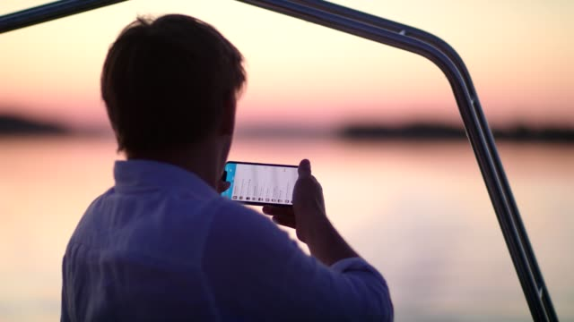 romantic sunset on a lake. young making photo from a boat - barca da diporto video stock e b–roll