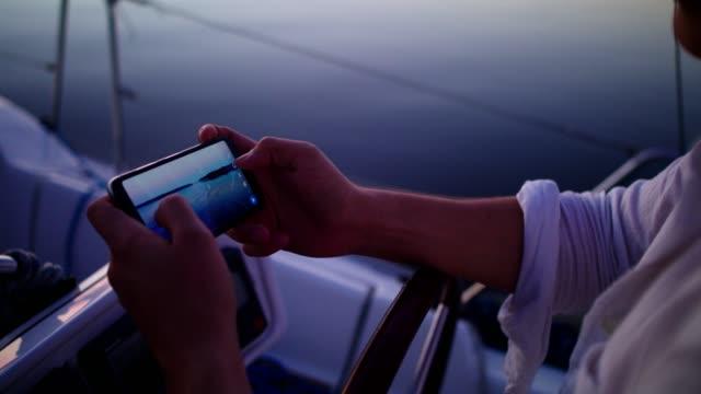 湖でロマンチックな夕日.ボートからの若いメイキング写真 - 船員点の映像素材/bロール