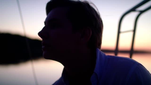 湖でロマンチックな夕日.セーリングを楽しむ若い男 - アウトドア点の映像素材/bロール