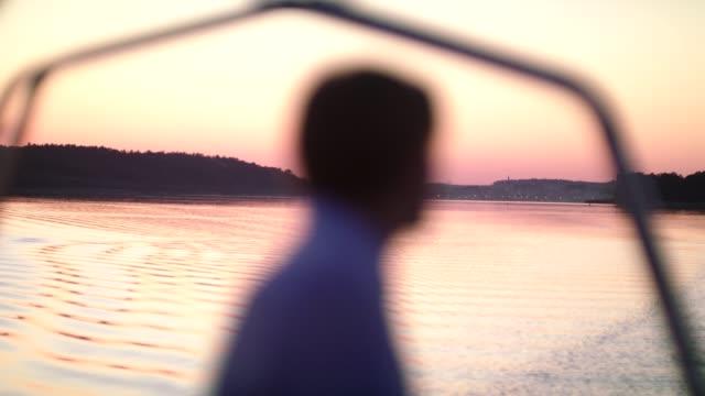 湖でロマンチックな夕日.ボートから視界を見ている若い男 - アウトドア点の映像素材/bロール