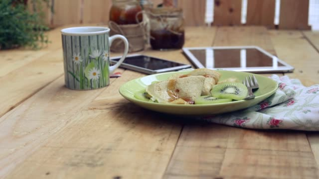 Romantic table outdoors with crepes with kiwi and honey