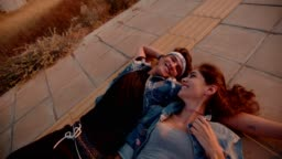 Romantic teenage couple of hipsters flirting lying down on pavement