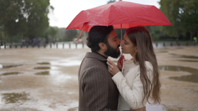 a romantic young couple together under an umbrella in the rain kissing - face to face stock videos & royalty-free footage