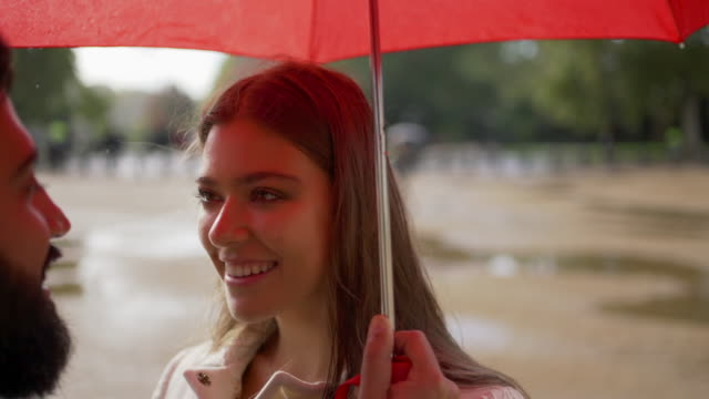 a romantic young couple together under an umbrella in the rain looking and smilling at each other - face to face stock videos & royalty-free footage
