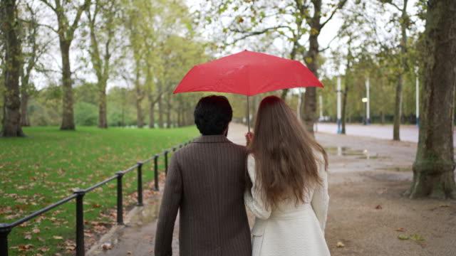 stockvideo's en b-roll-footage met een romantisch jong stel samen wandelen met een paraplu in de regen weg van de camera - paraplu