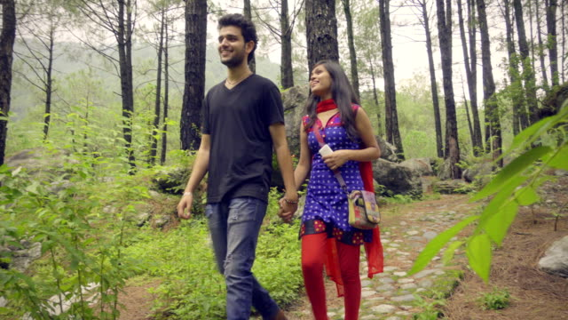 Romantic young couple walking in nature parkland.