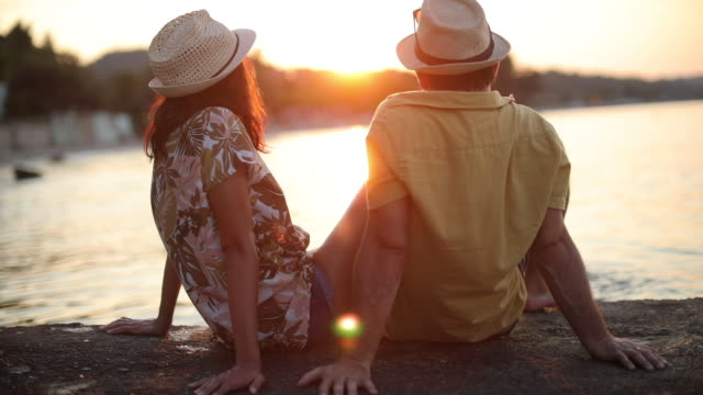 romantic young couple watching sunset by the sea - greece stock videos & royalty-free footage