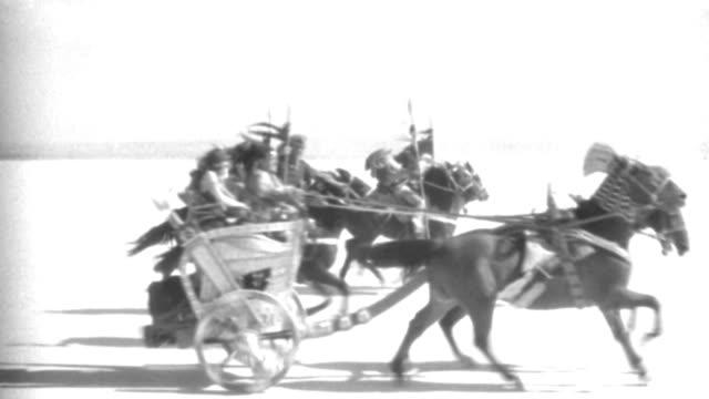 vídeos y material grabado en eventos de stock de dx - rome - m.s. - travel as chariots and riders l to r - stop - they exit r - b&w. - soldado romano