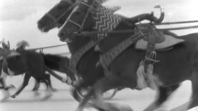vídeos y material grabado en eventos de stock de dx - rome - riders seen at start - travel - speed l with wheels chariots and feet horses - then to c.s. chariots and horses - to c.u. nearest pair horses - b&w. - soldado romano