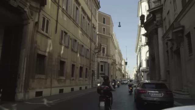 vídeos de stock e filmes b-roll de rome, scooters drive narrow roman street - capacete moto