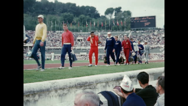 1960 rome summer olympics  - athletes walk onto track in olympic stadium - 1960 stock-videos und b-roll-filmmaterial