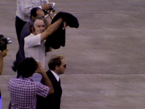 Ronald Biggs waves and blows a kiss at journalists as he walks across the runway at Brasilia airport